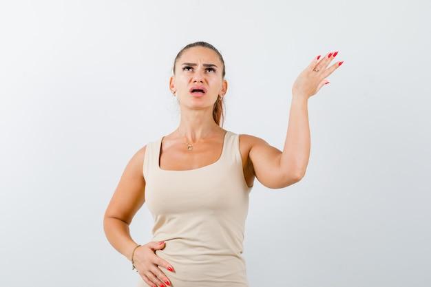 Jeune femme en débardeur beige qui s'étend de la main en geste de questionnement et à la perplexité, vue de face.