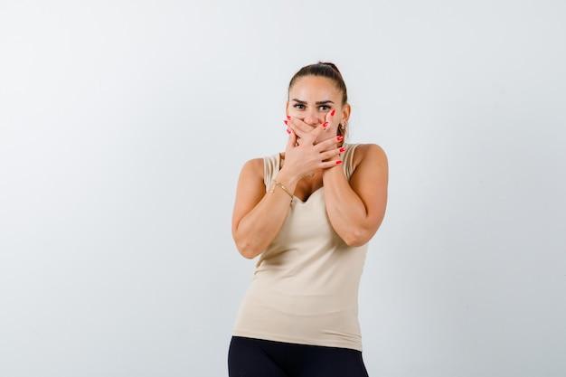 Jeune femme en débardeur beige tenant la main sur la bouche et à la perplexité, vue de face.