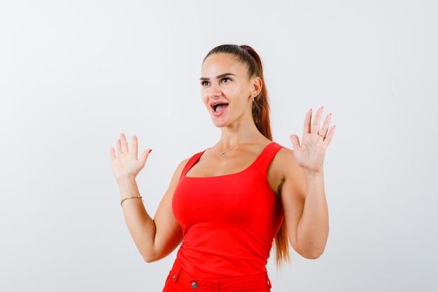 Jeune femme en débardeur rouge, pantalon montrant les paumes en geste de reddition et à la perplexité, vue de face.