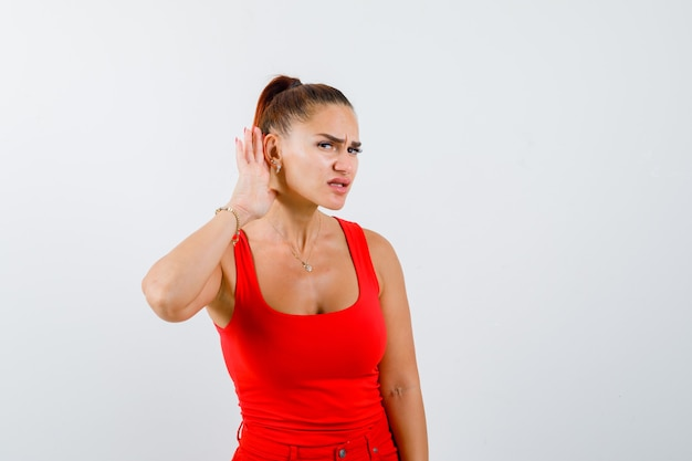 Jeune femme en débardeur rouge, pantalon tenant la main derrière l'oreille et regardant focalisé, vue de face.