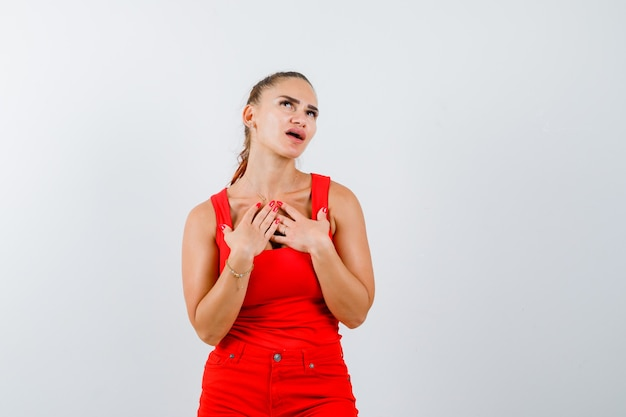 Jeune femme en débardeur rouge, pantalon tenant les mains sur la poitrine et à la vue fatiguée, de face.