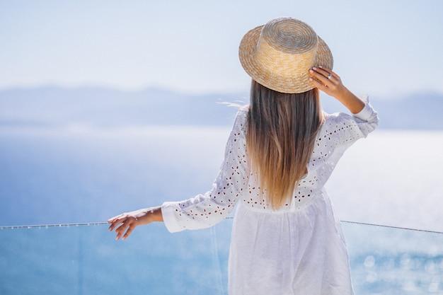 Jeune femme debout à l'arrière et regardant la mer