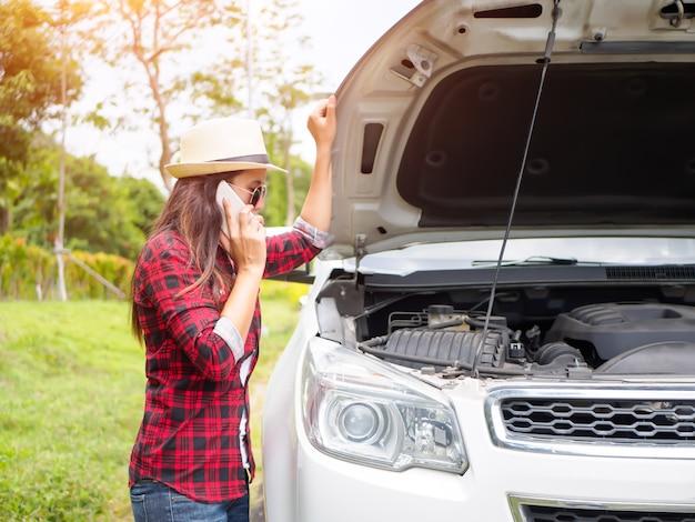 Jeune femme debout sur le bord de la route avec une voiture cassée.