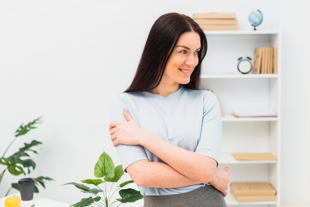 Jeune femme debout avec les bras croisés au bureau