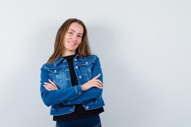 Jeune femme debout avec les bras croisés en blouse, veste et l'air confiant, vue de face.