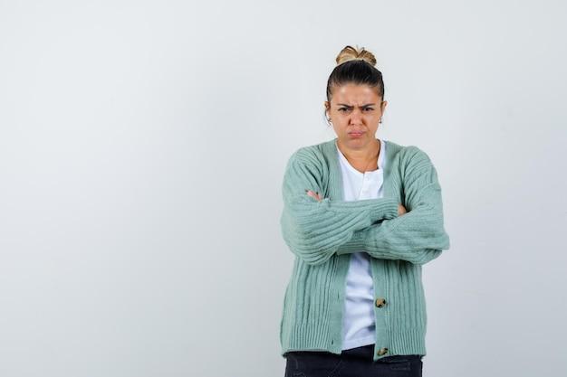 Jeune femme debout les bras croisés en chemise blanche et cardigan vert menthe et à la colère