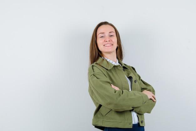 Jeune femme debout avec les bras croisés en chemise, veste et à l'air confiant. vue de face.