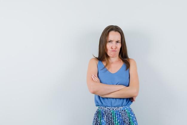 Jeune femme debout avec les bras croisés en maillot, jupe et à la recherche têtue. vue de face.