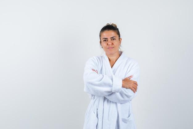 Jeune femme debout avec les bras croisés en peignoir et à la confiance