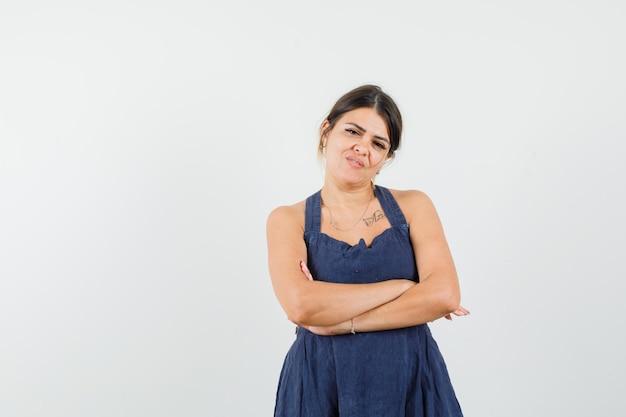 Jeune femme debout avec les bras croisés en robe et à la confiance