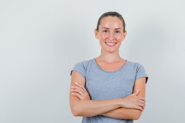 Jeune femme debout avec les bras croisés en t-shirt gris et à la joyeuse. vue de face.