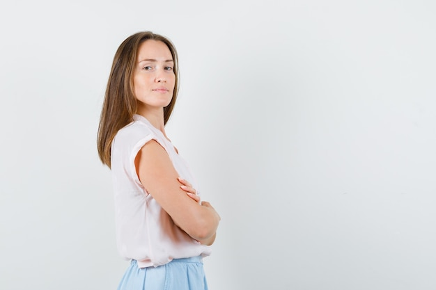 Jeune femme debout avec les bras croisés en t-shirt, jupe et à la confiance. .