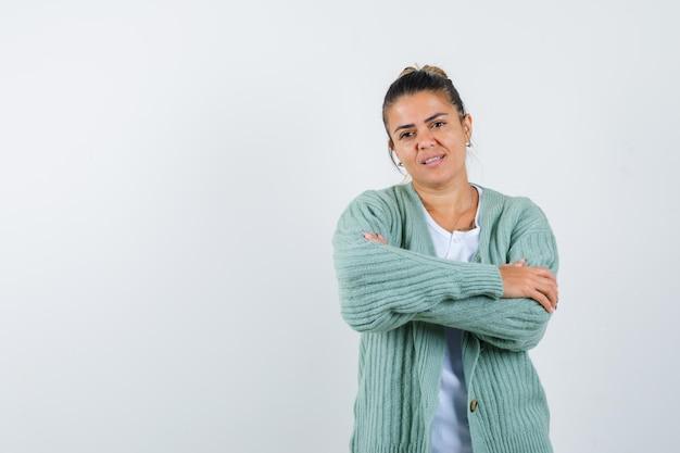 Jeune femme debout avec les bras croisés en t-shirt, veste et jolie