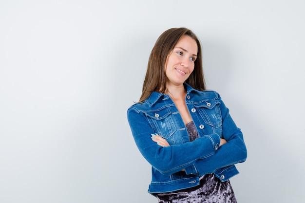 Jeune femme debout avec les bras croisés tout en détournant les yeux en blouse, veste en jean et l'air heureux. vue de face.