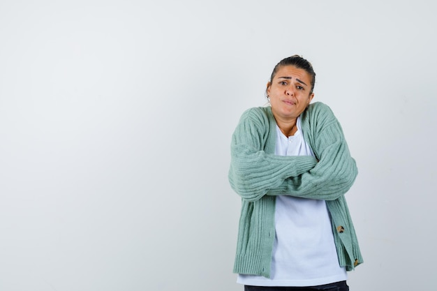 Jeune femme debout avec les bras croisés tout en haussant les épaules en t-shirt, veste et à l'air nostalgique