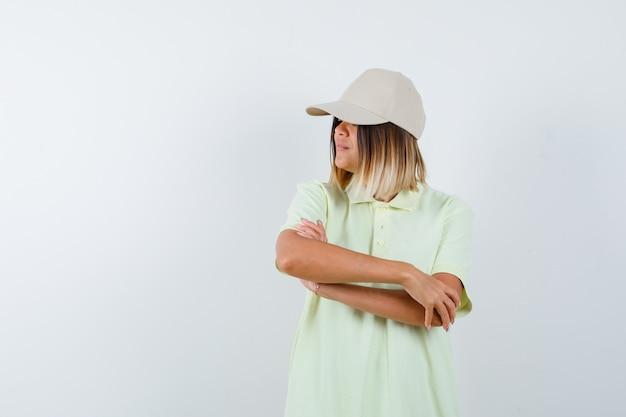 Jeune femme debout avec les bras croisés tout en regardant ailleurs en t-shirt, casquette et à la vue de face, confiant.