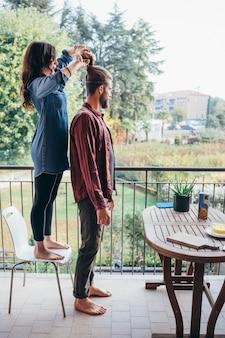 Jeune femme, debout, sur, a, chaise, faire, chignon cheveux, à, elle, plus grand, petit ami