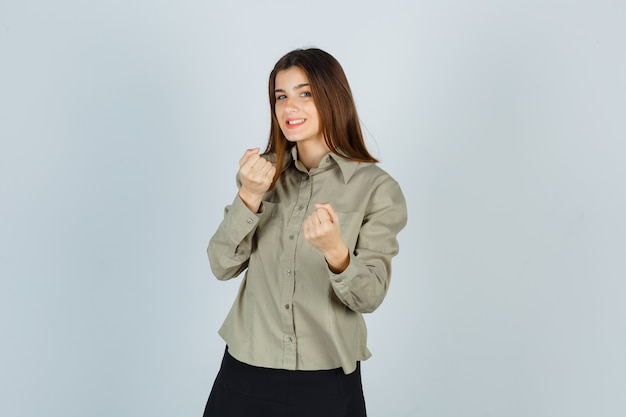 Jeune femme debout en combat pose en chemise, jupe et à la joyeuse