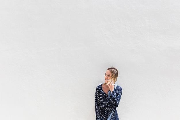 Jeune femme debout contre un mur blanc parlant sur téléphone portable