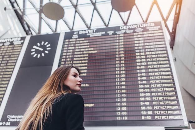 Jeune femme debout contre le tableau de bord de vol à l'aéroport