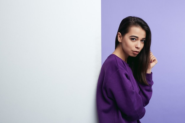 Jeune femme debout à côté du mur de panneau d'affichage blanc vide