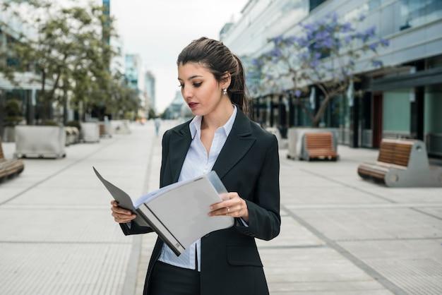 Jeune femme debout dans le campus d'affaires lisant le dossier