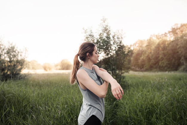 Jeune femme debout dans le champ herbeux qui s'étend de sa main