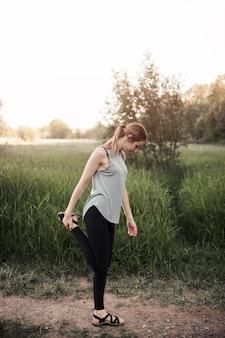 Jeune femme debout dans le champ qui s'étend de sa jambe