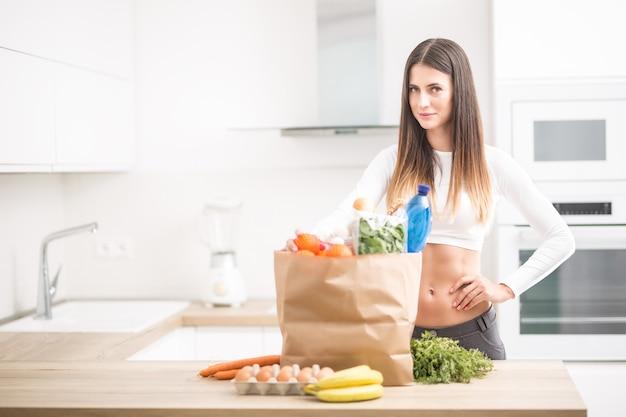 Jeune femme debout dans la cuisine avec achat sur table.