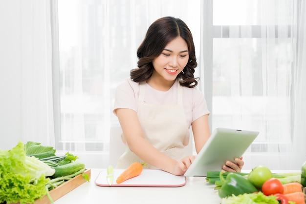 Jeune femme debout dans la cuisine avec tablette, ayant une idée et à la recherche de recettes dans la cuisine. vue de côté