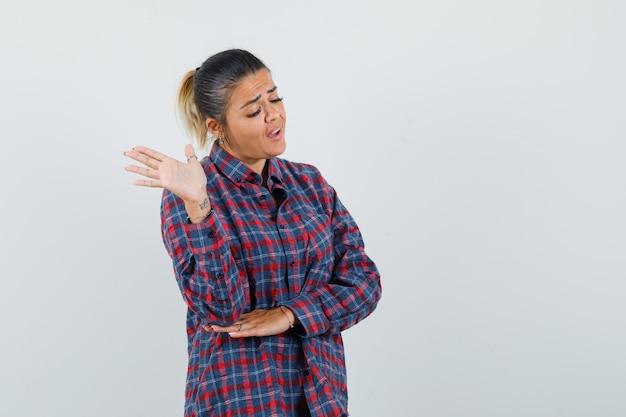 Jeune femme debout dans la pensée pose en chemise à carreaux et à l'ennui. vue de face.