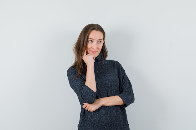 Jeune femme debout dans la pensée pose en chemise et à la joyeuse