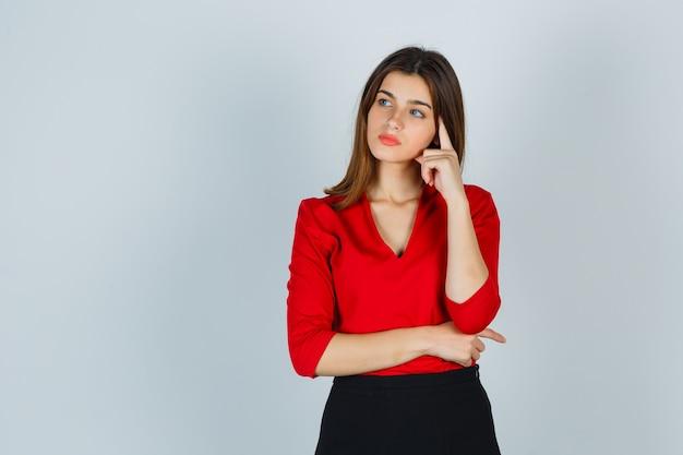 Jeune femme debout dans la pensée pose en chemisier rouge, jupe et à la pensif