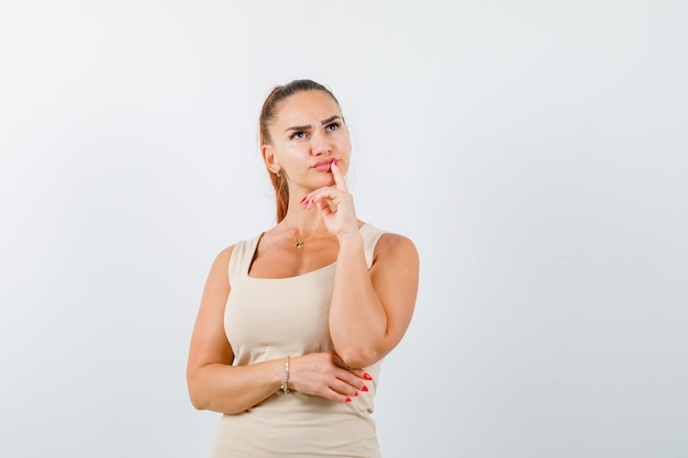 Jeune femme debout dans la pensée pose en débardeur beige et à la pensif. vue de face.