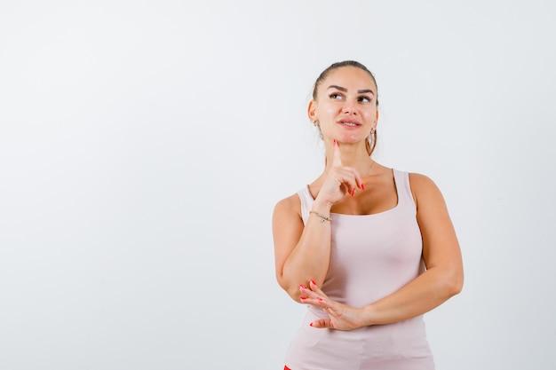 Jeune femme debout dans la pensée pose en maillot et à la recherche attentionnée, vue de face.