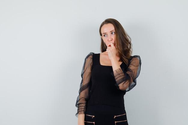 Jeune femme debout dans la pensée pose et mettant l'index sur la bouche en chemisier noir et pantalon noir et à la vue pensive, de face.