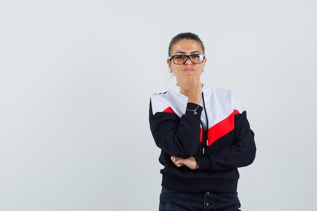 Jeune femme debout dans la pensée pose, mettant la main sous le menton en pull, jeans noirs et lunettes et à la jolie. vue de face.