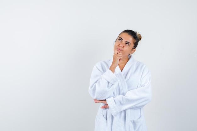 Jeune femme debout dans la pensée pose en peignoir et à la pensive