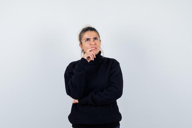 Jeune femme debout dans la pensée pose en pull à col roulé noir et à la pensif, vue de face.