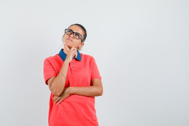 Jeune femme debout dans la pensée pose en t-shirt rouge et lunettes et à la pensif. vue de face.