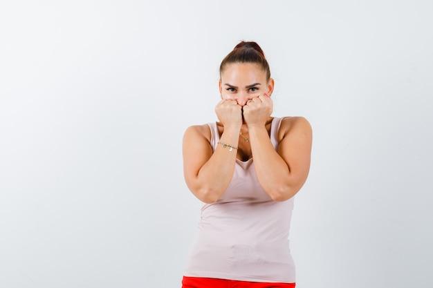 Jeune femme debout dans la peur pose en débardeur blanc, pantalon et à la peur. vue de face.