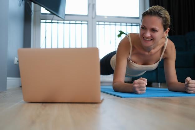 Jeune femme, debout, dans, planche, plancher, devant, ordinateur portable