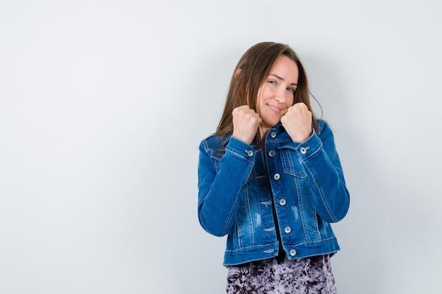 Jeune femme debout dans la pose de combat en chemisier, veste en jean et l'air confiant. vue de face.