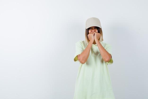 Jeune femme debout dans une pose effrayée en t-shirt, casquette et à la vue stressée, de face.
