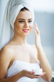 Jeune femme, debout, dans, salle bains, et, appliquer, crème visage, matin