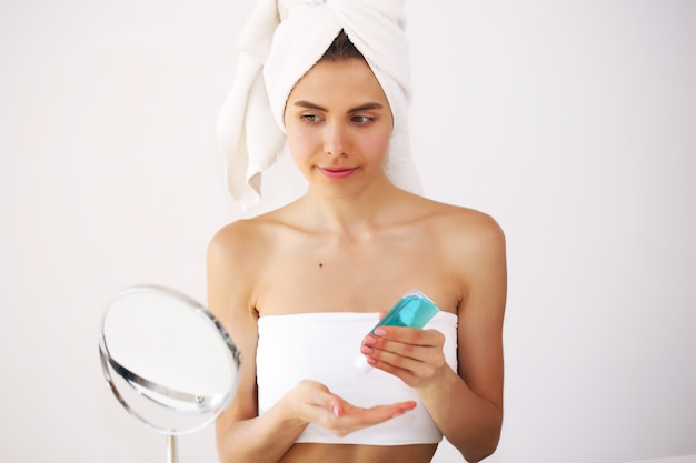 Jeune femme debout devant un miroir en prenant soin d'elle-même après un bain chaud.