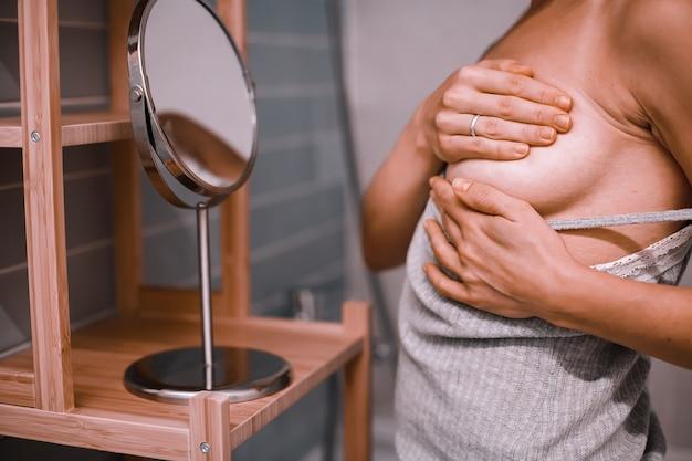 Jeune femme debout devant le miroir, vérifiant sa poitrine pendant l'auto-examen. la sensibilisation au cancer du sein. comment puis-je vérifier le concept du sein.