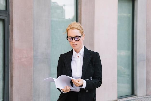 Jeune femme, debout, devant, mur, lecture documents