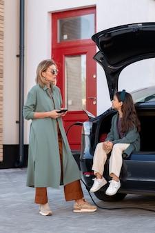 Jeune femme debout devant sa fille assise dans le coffre de la voiture