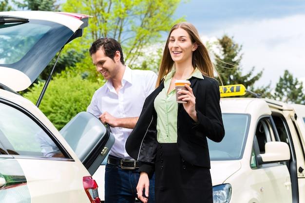 Jeune femme debout devant un taxi, elle a atteint sa destination, le chauffeur de taxi aidera avec les bagages
